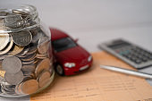 Car with coins in glass jar; car loan, finance, saving money, banking, insurance and leasing time concepts.