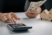 Woman presses a calculator and holding dollar bill to calculate the value during rental or purchase. Buying, Renting home, Purchase housing, Real estate concept.