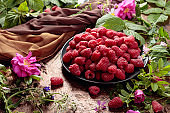 Summer still life with, raspberries, flowers and meadow grasses.
