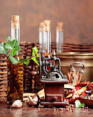 Old pepper mill with cooking utensils, bottles of olive oil, spices and rosemary on a wooden table.