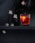 A glass of whiskey and falling ice pieces.