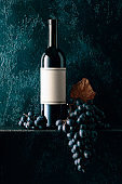 Red wine and blue grapes with dried up vine leaves on an old dark blue background.