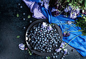 Summer still life with blueberries, colored sweet peas and meadow grasses on a dark blue table.