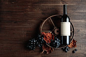 Bottle of red wine with an old rusty wheel.