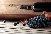 Bottle of red wine and a bunch of grapes on an old wooden table in the wine cellar.