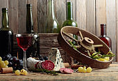 Rustic still life with red wine and snacks.