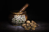 handmade wooden mortar with alpine decorations and nuts to beat