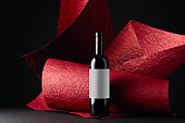 Unopened red wine bottle with empty label.