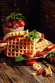 Waffles with strawberries and mint on a wooden table.