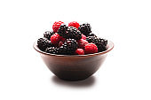 Raspberry, blackberry and mint leaf in ceramic brown bowl isolated on white