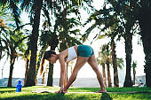 Young Caucasian woman 20s in active wear standing in pose recreating and feeling inspiration outdoors, female stretching in asana have yoga training for relaxing in sunny park with palm trees