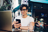 Cheerful male blogger reading message on mobile phone chatting in social networks on remote jobm happy businessman satisfied with online project income checking banking notification on smartphone