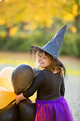 Happy little girl celebrates Halloween outdoors. Child in witch costume and hat with orange and black balloons in autumn park