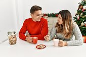 Young couple smiling happy sitting on the table having breakfast at home.