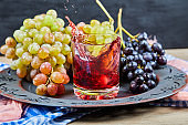 Bunch of grapes and a glass of juice on dark background