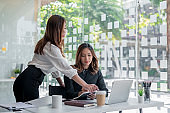 Two young asian businesswoman discussing new business projects during at office meeting.