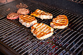 beef steak cooking over flaming grill.grilled meat skewers, barbecue.Delicious cooked meat. summer season. garden party.pork steak