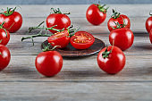 Bunch of fresh juicy tomatoes and slices of tomato on wooden table