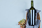 Bunch of grapes and a bottle of wine on gray background