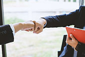 Young asian businessman partners fist bump showing cooperation and success at work.