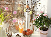 Happy Easter concept, spring card, composition with tulips, pussy willow and eggs on a bright sunny window, background, banner for the screen,