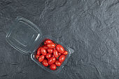 Red small tomatoes in plastic container on black background
