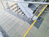 modern metal staircase.Looking down at a modern staircase with white wall as to be found in an office, hospital or an apartment.sunny day.yellow line helps visually impaired the indoor stairway
