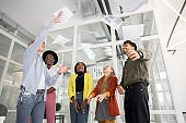Startup creative multiracial team throwing up documents after meeting