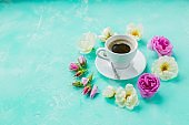 Morning Cup of coffee and a beautiful roses flowers on light background, top view. Cozy Breakfast. Flat lay style.Flat lay home workspace background.copy space on blue background. Cozy breakfast