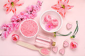 Spa and wellness composition with aromatic rose water, salt, roses and sakura, towels, aromatherapy and skin care, lifestyle concept, invitation and advertising card,