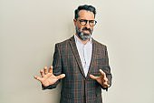 Middle age man with beard and grey hair wearing business jacket and glasses disgusted expression, displeased and fearful doing disgust face because aversion reaction. with hands raised