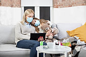 Isolation, desease, infection, coronavirus and quarantine concept. Sick young loving mother and teen daughter in protective masks, sitting together on sofa in living-room and using tablet pc