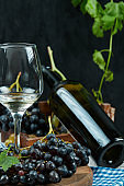 A bunch of black grapes with a glass of wine and a bottle on dark background