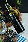 A bunch of grapes with a glass of wine and a bottle on white table