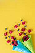 Ripe sweet raspberries and blueberries in ice cream waffle cones, copy space. Fresh and delicious berries on bright background. Summer and healthy food concept.Copy space