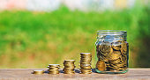 row of coin in bottle on wood table with blur nature park background. money saving concept for financial banking and accounting.