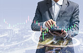 double exposure of business man using smartphone for trading stock online concept with night city background. technology digital financial with stock chart growth analysis marketing graph.