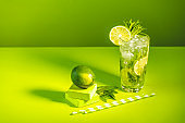 Creative drink background. Fresh Mojito cocktail with lime and mint in highball glass with water drops on green background in bright light, Mojito refreshing drinks. Summer vacation and party concept