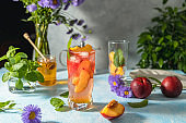 Peach infused water, cocktail, lemonade or tea. Summer iced cold drink with peach and mint on light gray table surface. Selective focus.