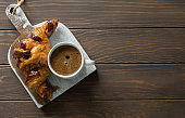 Croissant with  chocolate and cup of coffee on grunge cutting board close up