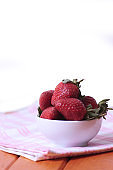 bowl of strawberries on a napkin on wooden table isolated on white background. Healthy eating concept