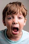 Screaming caucasian little boy On gray background
