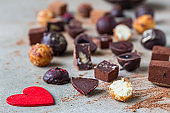 Variety of sweet homemade chocolate candies and truffles, light concrete background. Close up.
