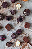 Variety of sweet homemade chocolate candies and truffles, light concrete background. Top view.