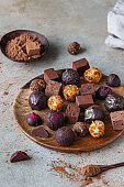 Chocolate truffles and candies on light stone background. Homemade dark chocolate truffles and candies with cocoa powder.