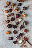 Chocolate truffles and candies on light stone background. Homemade dark chocolate truffles and candies with cocoa powder. Top view.