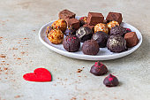 Variety of sweet homemade chocolate candies and truffles, light concrete background.