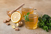 Hot mint and thyme tea with ginger root, lemon and honey, light concrete background. Herbal tea.