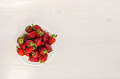 Strawberry on a white wooden background top view