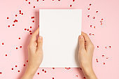 Woman hands holding blank Valentine card on pink table